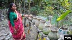 Một phụ nữ ở làng Chandipur cho xem những cây bí ngô bà trồng trong khu vườn trồng cách thẳng đứng của bà, một phương pháp giúp những người sống trong các vùng đất nhiễm mặn trồng rau củ