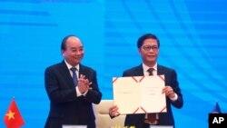 """越南總理阮春福(左)與越南貿易部長陳俊英在視訊簽署儀式上手持""""區域全面經濟夥伴關係""""簽署文件。"""