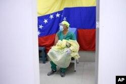Con una bandera de Venezuela de fondo, un médico espera recibir una dosis de la vacuna rusa COVID-19 Sputnik V en el hospital público Ana Francisca Pérez de León II en Caracas, Venezuela, el viernes 19 de febrero de 2021.