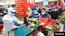 武汉爆发新型冠状病毒后,一名身穿防护服的工作人员在一家超市的收银台为顾客服务。(2020年2月12日)