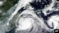This Sept. 1, 2020, satellite image released by NASA shows Typhoon Maysak over Japan's southernmost islands, including Okinawa, center.