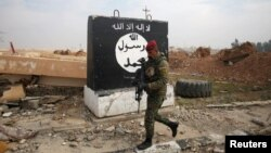 FILE - An Iraqi soldier walks next to a wall painted with the black flag commonly used by Islamic State militants, north of Mosul, Iraq, Jan. 21, 2017.