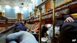 La gente se refugia en la galería de la Cámara mientras los manifestantes intentan irrumpir en la Cámara de la Cámara en el Capitolio de los Estados Unidos el miércoles 6 de enero de 2021 en Washington.