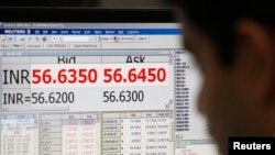 一名外幣交易員正在顯示印度貨幣盧比對美元的結算的電腦屏前工作。