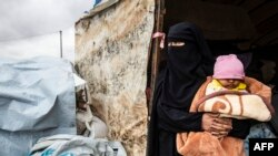 A Syrian woman carrying a baby looks out of a tent as she packs her belongings before leaving the Kurdish-run al-Hol camp holding relatives of alleged Islamic State group fighters, in the al-Hasakeh governorate in northeastern Syria, Nov. 16, 2020.