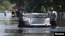 People use an air mattress to float possessions out of a flooded area of Port Arthur, Texas, Aug. 31, 2017. Health officials warn people to avoid floodwaters, which could be contaminated, electrified or hiding sharp objects.