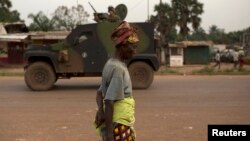 FILE - A woman walks past French peacekeeping soldiers patrolling in an armored vehicle, following continuing sectarian violence in the capital, Bangui, on Feb. 4, 2014.
