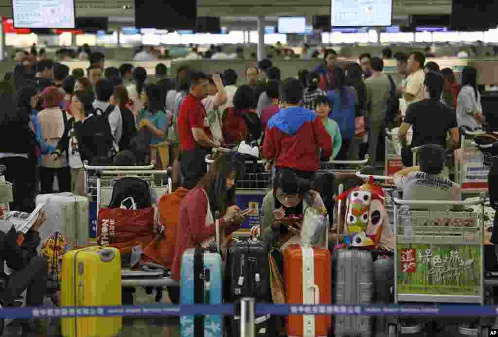 Para penumpang yang terpengaruh Topan Usagi menanti di bandar udara internasional Hong Kong (23/9). Lebih dari 370 penerbangan dibatalkan akibat topan ini. (AP/Vincent Yu)
