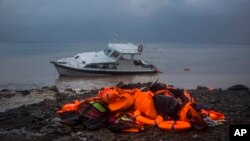 Life Jackets and a boat used by refugees and migrants to cross a part of the Aegean sea from Turkey to the Greek island of Lesbos remain on a beach, Thursday, Nov. 26, 2015.