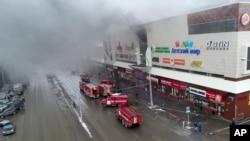 آتش زدگی کا نشانہ بننے والے شاپنگ مال سے دھواں اٹھ رہا ہے۔