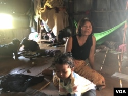 Om Samath, 53, a resident of Siem Reap City's Chreav commune, looks after her grandchildren while their parents are at work. March 15, 2019. (Sun Narin/VOA Khmer)