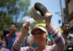 A woman bangs a pot to protest Venezuela's President Nicolas Maduro in Los Teques on the outskirts of Caracas, Venezuela, Sept. 7, 2016.