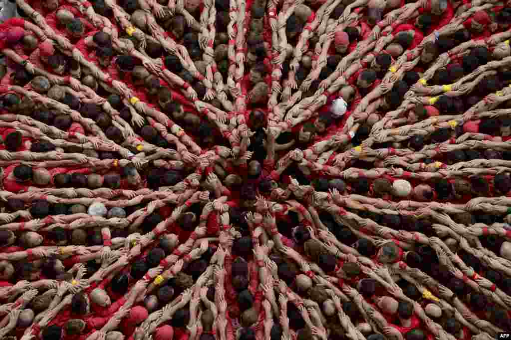 """Members of the """"Colla Vella Xiquets de Valls"""" human tower team form a """"castell"""" during the XXV human towers, or castells, competetion in Tarragona, Spain, Oct. 5, 2014."""