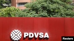 FILE - The corporate logo of the state oil company PDVSA is seen at a gas station in Caracas, Venezuela, Nov. 16, 2017.