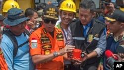 Predstavnici nacionalne Agencije za potragu i spasavanje pokazuju pronađenu crnu kutiju