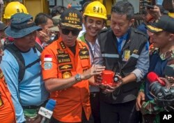 FILE - Chief of National Search and Rescue Agency Muhammad Syaugi, center, holds the flight data recorder from the crashed Lion Air jet during a press conference, onboard rescue ship anchored in the waters of Tanjung Karawang, Indonesia, Nov. 1, 2018