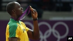 Pelari Jamaika, Usain Bolt, memegang medali emas yang diperolehnya setelah memenangkan cabang lari 200 meter di Stadion Olimpiade London (9/8).