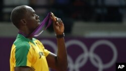 Jamaica's Usain Bolt holds up his gold medal for the men's 200-meter during the athletics in the Olympic Stadium at the 2012 Summer Olympics, London, August 9, 2012.