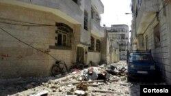 Puing-puing bangunan di dekat bangunan markas keamanan negara di Homs, Suriah.
