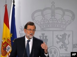 FILE - Spain's Prime Minister Mariano Rajoy gestures as he delivers a statement at the Moncloa Palace in Madrid, Spain, Oct. 11, 2017.