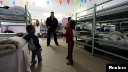 FILE - Father Rito Julio Alvarez plays with migrant children in the dormitory of San Antonio church in Ventimiglia, Italy, Oct. 3, 2016.