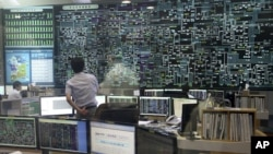 An employee of the Korea Power Exchange, a state company to check the country's flow of electricity, watches a huge screen monitoring power supply during power outages in Seoul, September 15, 2011.