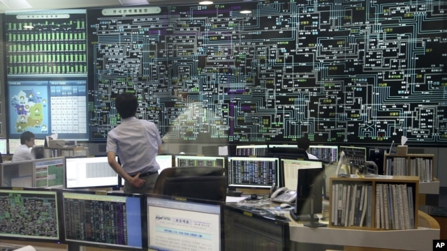 FILE - An employee of the Korea Power Exchange, a state company to check the country's flow of electricity, watches a huge screen monitoring power supply during power outages in Seoul, September 15, 2011.