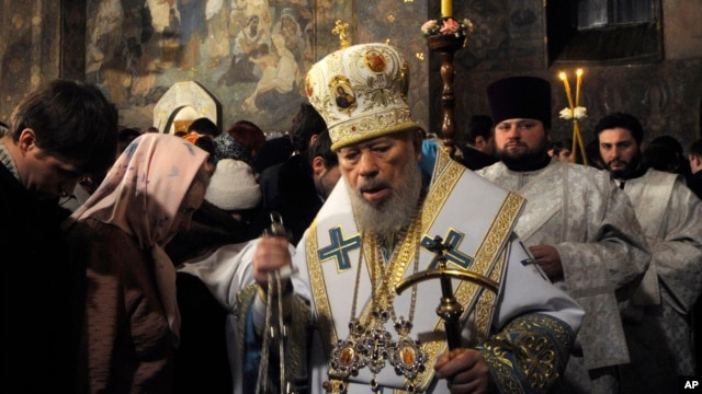 FILE - In this file photo taken Jan.  5, 2014, the head of the Ukrainian Orthodox Church under the Moscow Patriarchate, Volodymyr, foreground, leads services during the Christmas Eve mass in the Kyiv-Pechersk Lavra church in Kyiv.