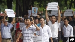 Anti-China protesters hold a portrait of late revolutionary leader Ho Chi Minh and the names of Vietnamese soldiers who were killed by China in 1974 in the Paracel Islands and in 1988 in the Spratly Islands during a demonstration in Hanoi, July 24, 2011.