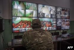 Un oficial sirio vigila por cámaras de circuito cerrado a centenares de prisioneros sospechosos de ser combatientes de ISIS.