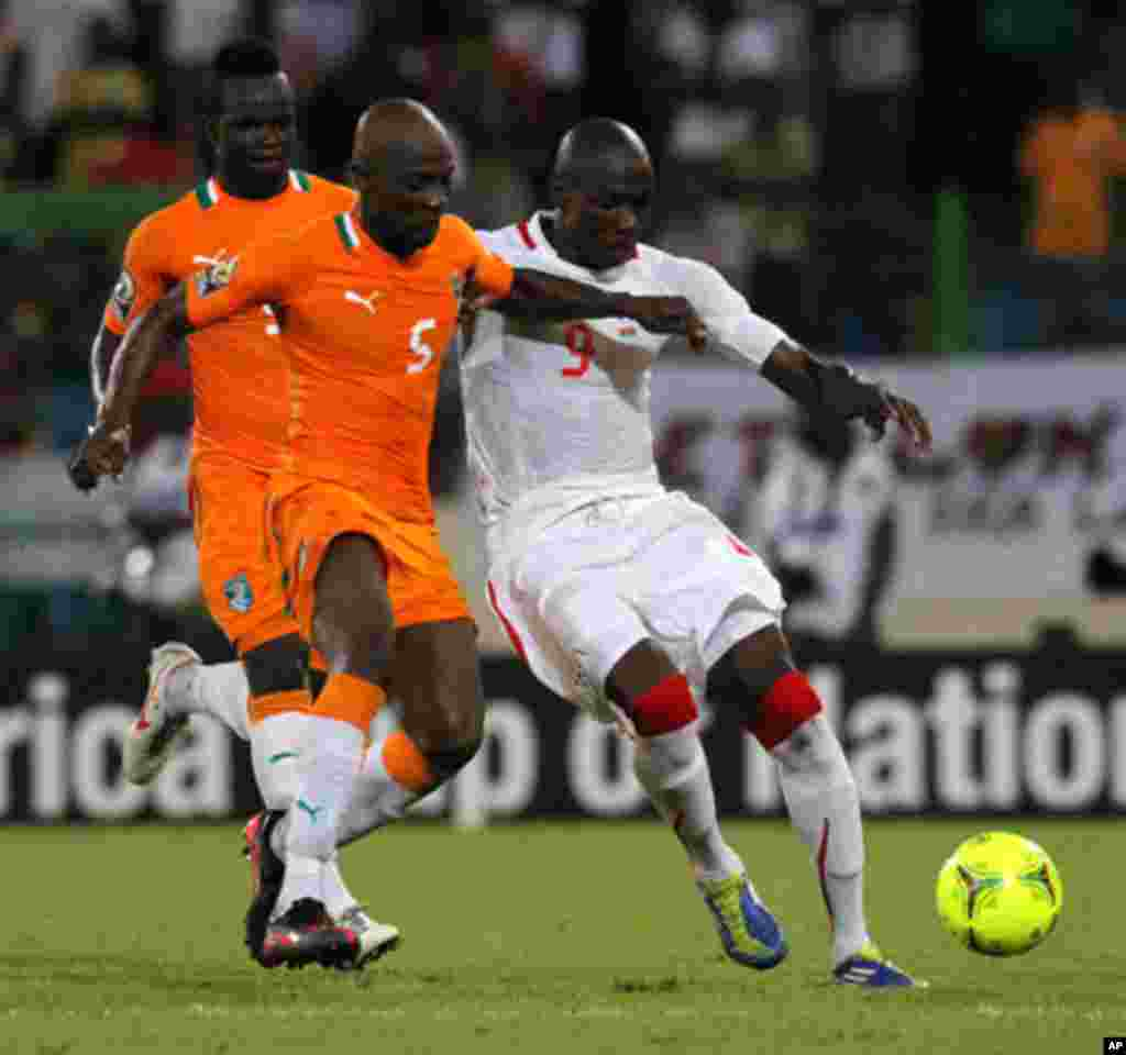 Didier of Ivory Coast fights for the ball with Moumouni of Burkina Faso during their African Nations Cup soccer match in Malabo