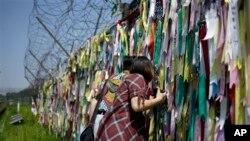 Pengunjung mengintip dari pagar kawat yang dihiasi pita bertuliskan pesan-pesan reunifikasi kedua Korea, di Paviliun Imjingak dekat desa perbatasan Panmunjom. (AP/Lee Jin-man)