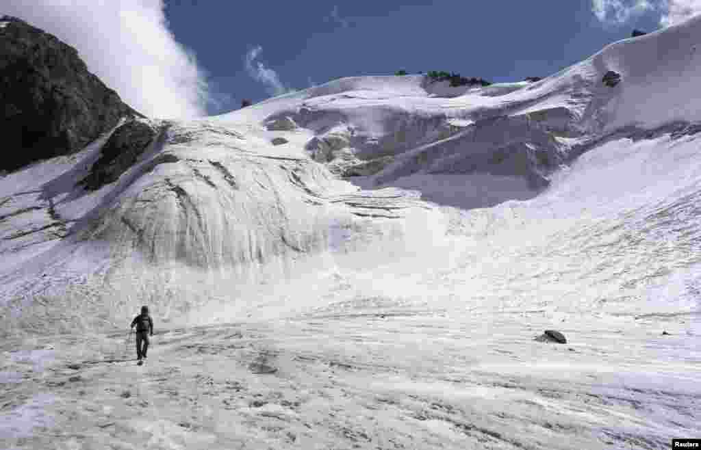 Seorang turis berjalan dekat glasier Manshuk Mametova, pada ketinggian 3.550 meter di atas permukaan air laut, di gunung Tien Shan, di luar Almaty, Kazakhstan.