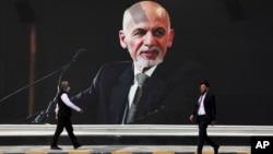 Men walk past a mural of President Ashraf Ghani at Hamid Karzai International Airport, in Kabul, Afghanistan, Aug. 14, 2021.