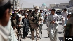 Tentara NATO berbincang dengan warga setempat di kota Kandahar.