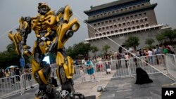 "A child stands on a barricade fence looks at a replica model of Transformers character Bumblebee on display in front of Qianmen Gate, as part of a promotion of the movie ""Transformers: Age of Extinction"" in Beijing, China, June 21, 2014."