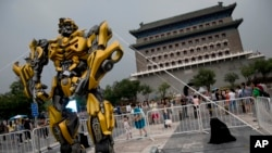 "FILE - A child stands on a barricade fence looks at a replica model of Transformers character Bumblebee on display in front of Qianmen Gate, as part of a promotion of the movie ""Transformers: Age of Extinction"" in Beijing, China."