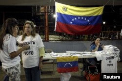 """FILE - Venezuelans supporting Venezuelan opposition leader Henrique Capriles wear T-shirts that read """"Count my Vote"""" during a gathering for a petition in Panama City, Panama, April 17, 2013."""