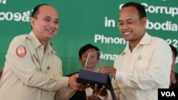 Om Yentieng, head of the government Anti-Corruption Unit, hands award to an outstanding reporter on corruption in Phnom Penh, July 22, 2015. (Hean Socheata/VOA Khmer)