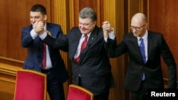 FILE - Ukraine's President Petro Poroshenko, center, holds up the hands of newly appointed Prime Minister Arseny Yatseniuk, right, and newly appointed Parliament Speaker Volodymyr Groysman during a parliament session in Kyiv, Nov. 27, 2014.