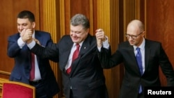 Ukraine's President Petro Poroshenko, center, holds up the hands of newly appointed Prime Minister Arseny Yatsenyuk, right, and newly appointed Parliament Speaker Volodymyr Groysman during a parliament session in Kyiv, Nov. 27, 2014.