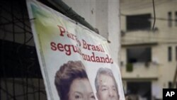 A campaign poster for Workers Party presidential candidate Dilma Rousseff, left, with Brazil's President Luiz Inacio Lula da Silva sits in the Andarai slum in Rio de Janeiro, Brazil, 01 Oct 2010