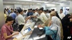فائل فوٹو۔ اسلام آباد، پاکستان میں لوگ فری موبائل فون کنکشن کے لیے ایک موبائل فون کمپنی کے آفس میں قطار بنائے کھڑے ہیں۔