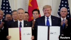 "U.S. President Donald Trump stands Chinese Vice Premier Liu He after signing ""phase one"" of the U.S.-China trade agreement in the East Room of the White House in Washington, U.S., January 15, 2020"