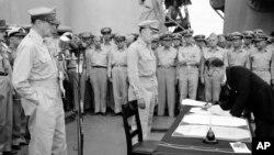 Ministar spoljnih poslova Japana Manoru Šigemicu potpisuje dokument o kapitulaciji svoje zemlje u Drugom svetskom ratu. Posmatraju ga američki generali Daglas Mekartur (levo) i Ričard K. Saterlend, dok su u pozadini drugi američki i britanski oficiri (Foto: AP/C.P. Gorry)