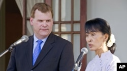Nobel laureate Aung San Suu Kyi listens to Canadian Foreign Affairs Minister John Baird following a meeting at her home in Rangoon, Burma, March 8, 2012.