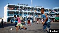 Bocah-bocah Palestina bermain bola di tempat penampungan mereka di sebuah sekolah milik PBB di Jabaliya, Jalur Gaza (31/7/2014).