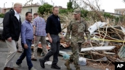 FILE - President Donald Trump walks with FEMA administrator Brock Long, second from right, and Lt. Gen. Jeff Buchanan, right as he tours an area affected by Hurricane Maria in Guaynabo, Puerto Rico, Oct. 3, 2017.