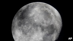 In this early Monday, Oct. 5, 2020, file photo, a waning moon is seen at the sky over Frankfurt, Germany. The moon's shadowed, frigid nooks and crannies may hold frozen water in more places and in larger quantities than previously suspected. (AP Photo/Michael Probst, File)