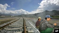 Para pekerja tengah beristirahat di dekat rel kereta api di stasiun Lhasa, Tibet, China (Foto: dok). Lebih dari 100 pengunjuk rasa menyerang polisi dan membakar kendaraan di kabupaten Linshui di propinsi Sichuan, Sabtu (16/5), memprotes rencana proyek jalur kereta api.